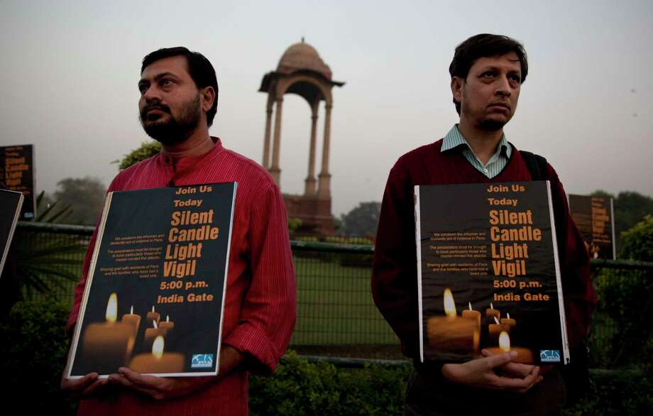 """Indians participate in a vigil in remembrance of victims of Friday's attacks in Paris, France, in New Delhi, India, Saturday, Nov. 14, 2015. Indian Prime Minister Narendra Modi, on a visit to the United Kingdom, said he condemned """"the barbaric terrorist attacks in Paris in the strongest terms."""" Photo: AP Photo/Tsering Topgyal    / AP"""