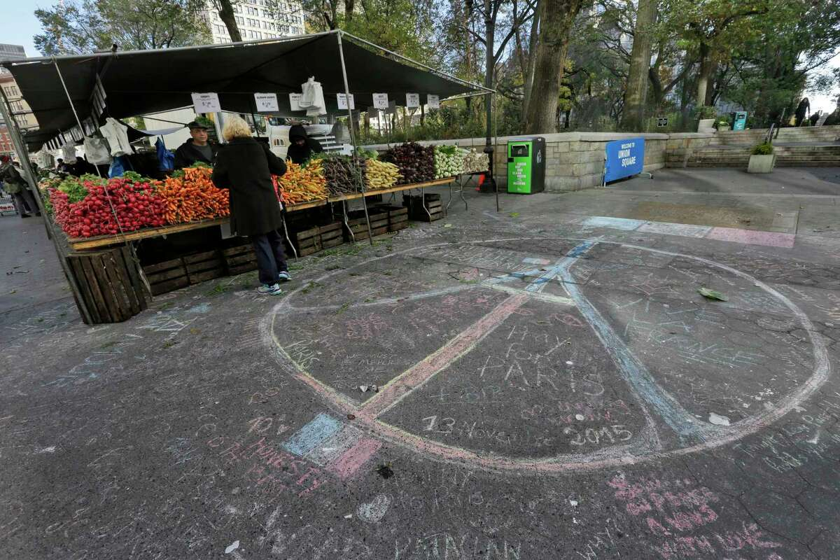 A woman shops for produce next to a peace sign drawn in solidarity to the people of Paris at the framers market in New York's Union Square, Saturday, Nov. 14, 2015. French officials say several dozen people were killed in shootings and explosions at a theater, restaurant and elsewhere in Paris on Friday.