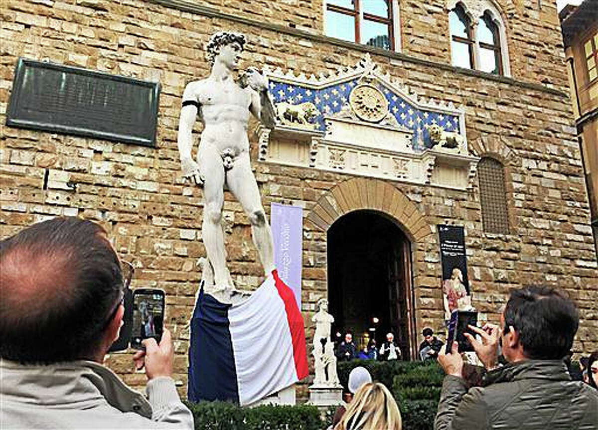 Tourists take pictures of a copy of Michelangelo's David adorned with a French flag and a black ribbon attached on the sculpture's right arm, in Florence, Italy, Saturday, Nov. 14, 2015. French police on Saturday hunted possible accomplices of eight assailants who terrorized Paris concert-goers, cafe diners and soccer fans with a coordinated string of suicide bombings and shootings in France's deadliest peacetime attacks. (AP Photo/Beatrice Larco)