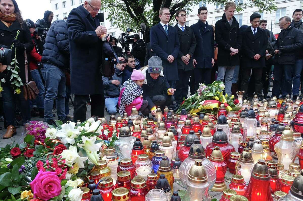People lay flowers and light candles for the victims of the deadly attacks in Paris, outside the French embassy in Warsaw, Poland, Saturday, Nov. 14, 2015. French President Francois Hollande said more than 120 people died Friday night in shootings at Paris cafes, suicide bombings near France's national stadium and a hostage-taking slaughter inside a concert hall. (AP Photo/Alik Keplicz)