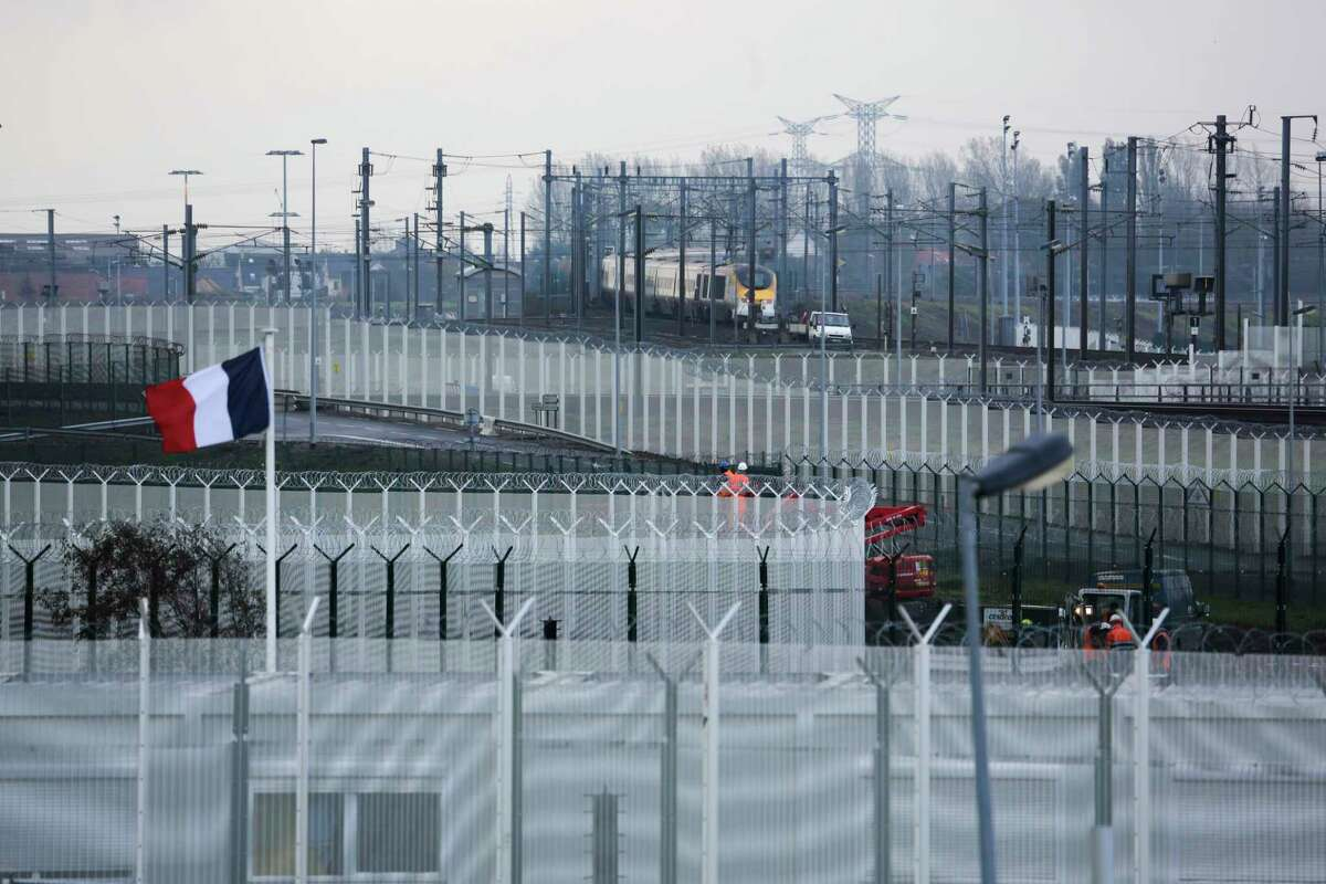 In this Wednesday, Nov. 4, 2015, photo the French national flag flutters between new build fences preventing migrants from reaching trains to Britain near Calais, northern France. Networks of newly constructed 15-foot-high (5-meter-high) razor-topped fences and boosted police patrols defeat many migrants hoping to cross the English Channel.