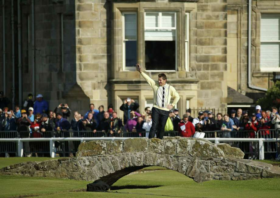 Nick Faldo waves to spectators as he stands on the Swilcan Bridge during the second round of the British Open on Friday. Photo: Jon Super — The Associated Press   / AP