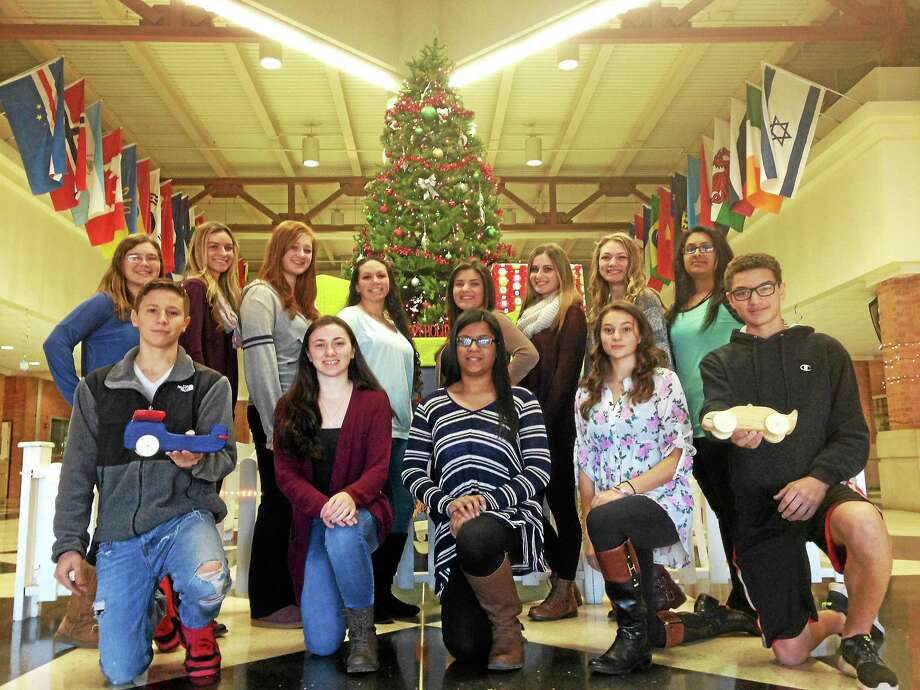 East Haven High School students from SADD, HOSA and the woodshop class pose in front of the school lobby's Christmas tree. The students organized a toy drive for children at Yale-New Haven Hospital. Photo: Juliemar Ortiz — New Haven Register