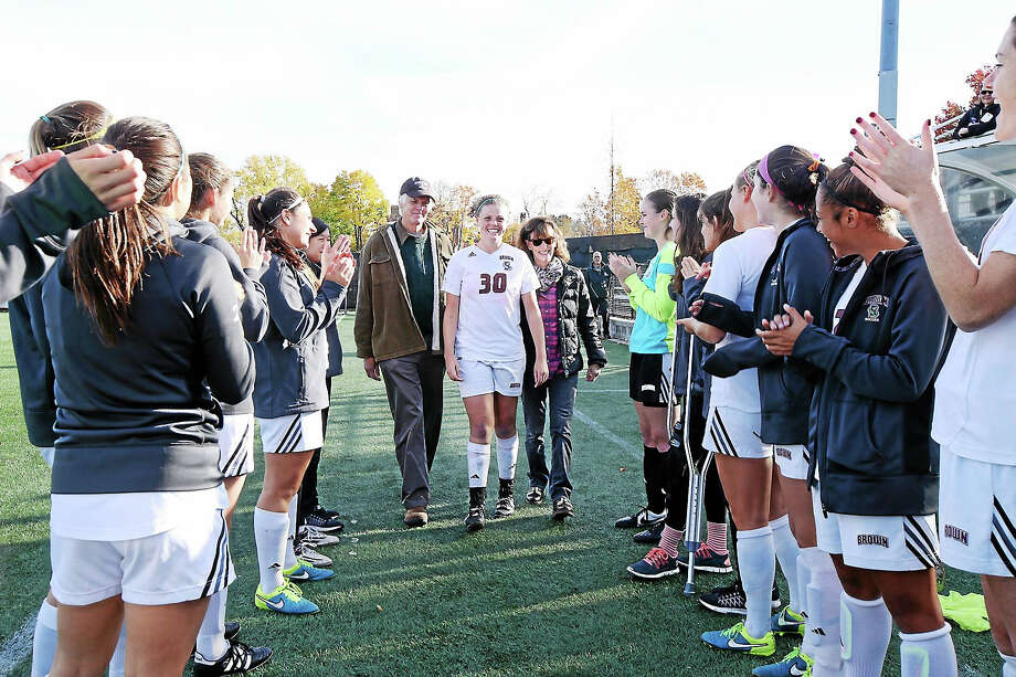 """Randall Beach and Jennifer Kaylin escort their daughter, Charlotte Beach, through a tunnel of her Brown University soccer teammates during """"Senior Day"""" recently at Brown Photo: David Silverman — Brown University Athletics"""