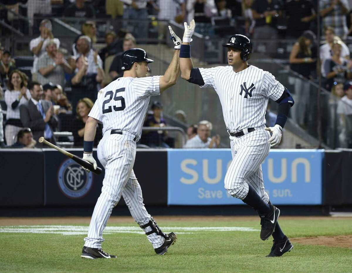 The Yankees' Mark Teixeira (25) greets Alex Rodriguez after Rodriguez hit a solo home run in the seventh inning that gave the Yankees a 4-3 win over the Mariners on Friday.