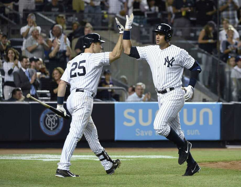 The Yankees' Mark Teixeira (25) greets Alex Rodriguez after Rodriguez hit a solo home run in the seventh inning that gave the Yankees a 4-3 win over the Mariners on Friday. Photo: Kathy Kmonicek  — The Assoiated Press   / FR170189 AP