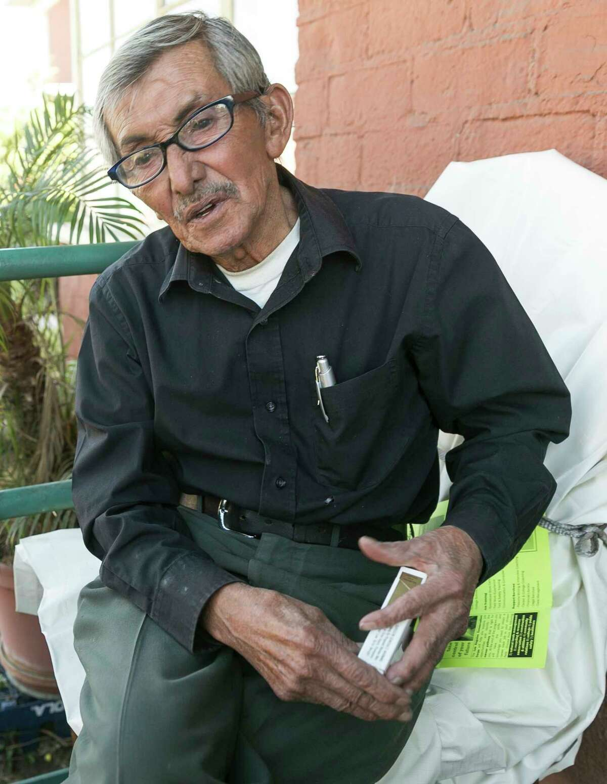 "Resident Juan Manuel Cabrera, 77, who has been smoking for 67 years, says no federal edict is going to stop him from lighting up in his own house at the William Mead Homes in Los Angeles, Thursday, Nov. 12, 2015. ""When I'm in my house I don't bother nobody and nobody bothers me,"" Cabrera said as he relaxed on his porch with his chubby brown Chihuahua, Dunko, an ashtray within arm's reach and a pack of Marlboro Lights in his pocket. The federal government's proposal Thursday to ban smoking inside and out of public housing nationwide got a decidedly mixed reaction from the people most affected."