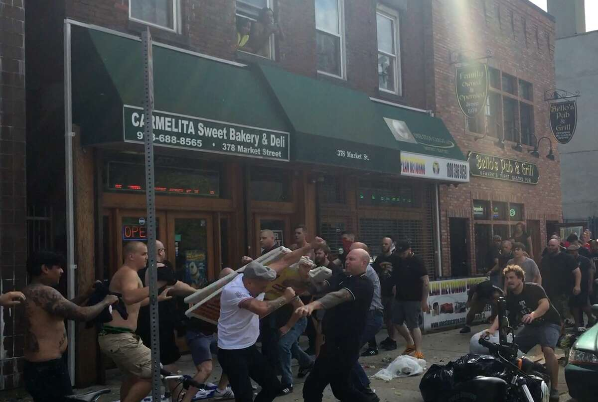 In this image made from video taken on Aug. 9, soccer supporters skirmish outside a pub ahead of the Major League Soccer match between the New York Bulls and New York City FC in Newark, New Jersey.