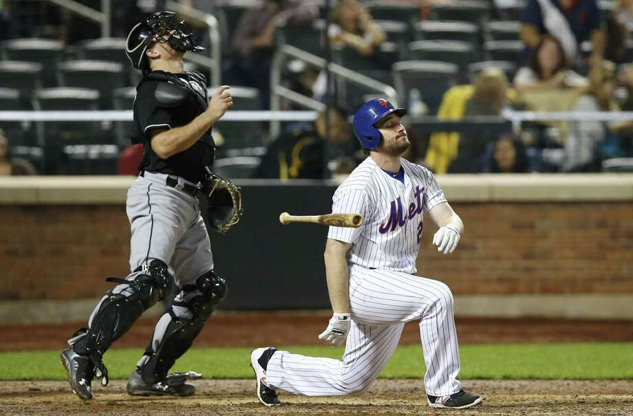 Miami Marlins catcher J.T. Realmuto, left, looks up as New York Mets' Daniel Murphy reacts after popping out to third for the second out in the ninth inning of a baseball game Tuesday, Sept. 15, 2015, in New York. The Marlins won 9-3. (AP Photo/Kathy Willens) Photo: AP / AP