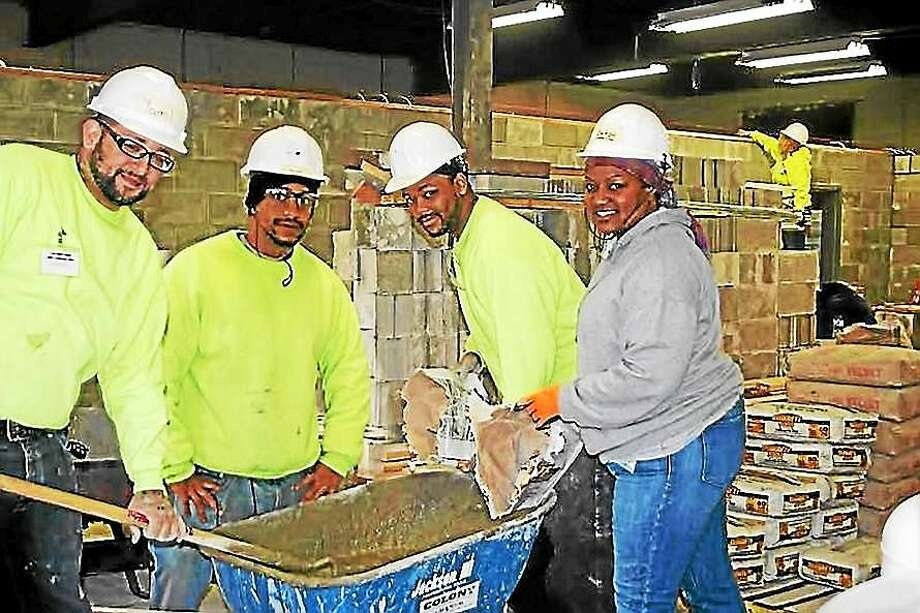 Students mix cement to install new walls at 316 Dixwell Ave. All the brick was donated. City officials are probing vandalism that was discovered earlier in the month. Photo: Contributed Photo