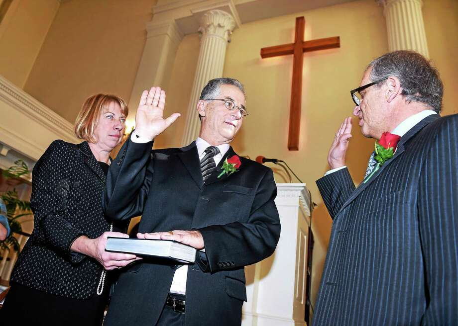 Karen Maturo (left) holds a bible for her husband, Joseph Maturo, Jr., (center) being sworn in as mayor of East Haven by attorney Lawrence Sgrignari at the Old Stone Church in East Haven on 11/14/2015. Photo: Arnold Gold — New Haven Register
