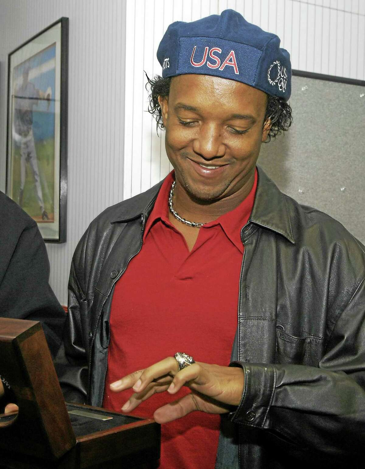 Pedro Martinez looks at his 2004 World Series ring.