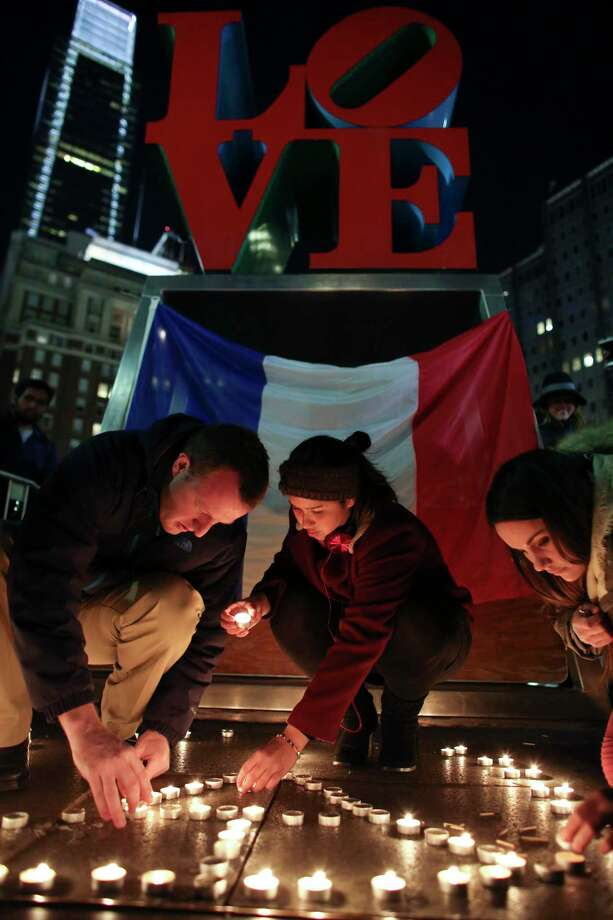 Stephane Fosik, from left, Cedrine Plongeur and Cloe Tinchant light candles in the shape of a peace symbol in LOVE Park, Saturday, Nov. 14, 2015, during a candlelight vigil to remember the victims of the attacks in Paris. Photo: AP Photo/Joseph Kaczmarek  / FR109827 AP