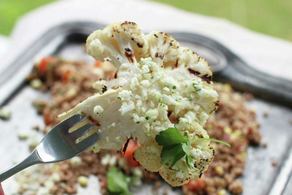 This June 8, 2015, file photo shows grilled cauliflower steaks with lemon lime feta gremolata in Concord, N.H. Back in 2013, the question was posed: Is cauliflower the new kale? It's 2015, people who have just discovered baked and roasted cauliflower, mashed cauliflower, cauliflower pasta sauce, cauliflower pizza crust and fancy arrangements of what is a fine food delicately plated in fine restaurants.