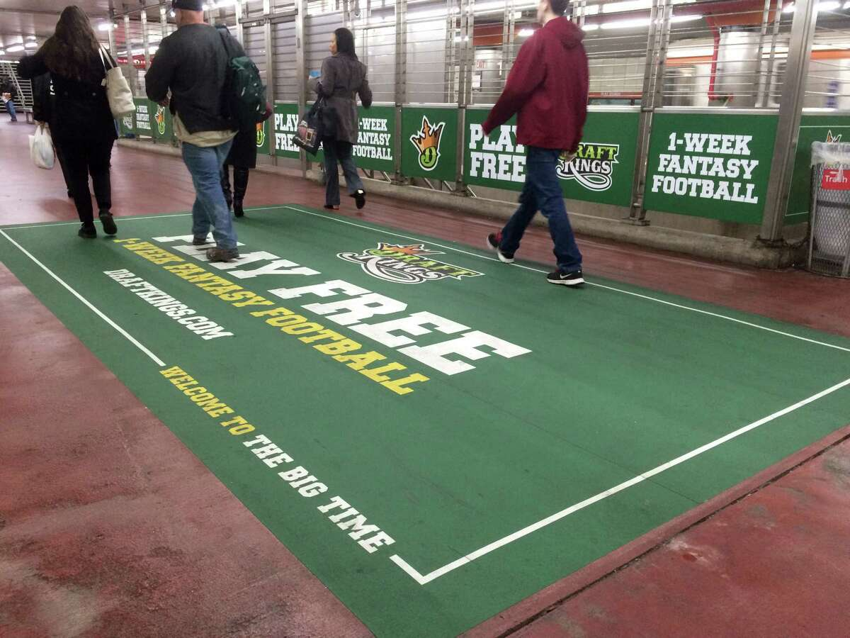 In this photo taken on Dec. 1, 2015, an ad for daily fantasy sports operator DraftKings is displayed in a subway station in Philadelphia. A state judge has barred daily fantasy sports sites DraftKings and FanDuel from doing business in New York.