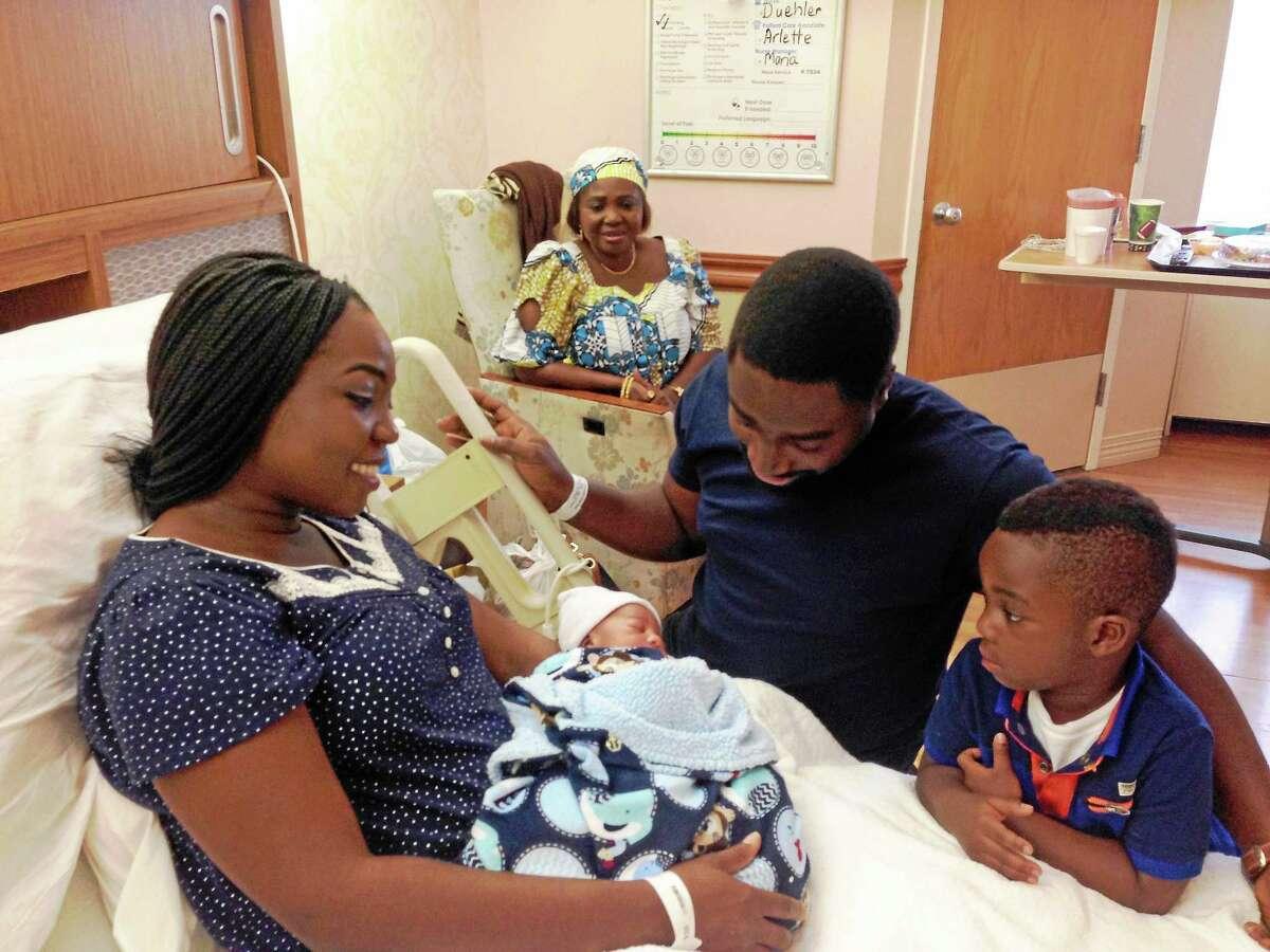 Aisha Aliyu, left, holding Timi, with her husband, Olamide Bamgboye, and son Fola, 3½. Aliyu's mother, Binta Aliyu, is at rear.