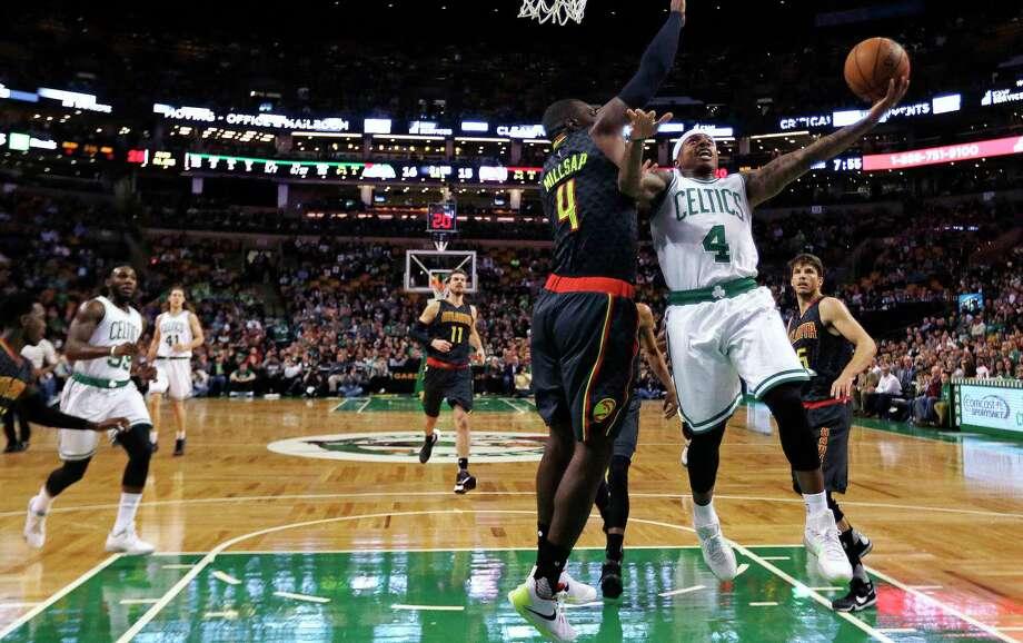 Celtics guard Isaiah Thomas (4) drives to the basket against Atlanta Hawks forward Paul Millsap (4) during Friday's game in Boston. Photo: Charles Krupa — The Associated Press   / AP