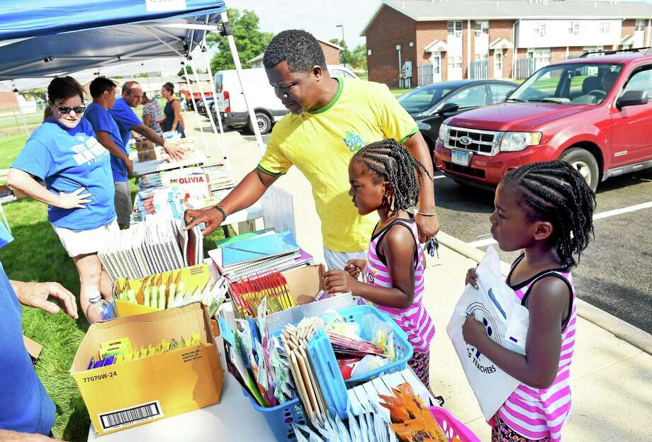 Left to right, Reuben Walters picks out school supplies with his twin daughters, Reunell and Reunick, 5, at Meadow Landing Apartments in West Haven Monday. The Walters twins will be going into first grade. Photo: Arnold Gold — New Haven Register