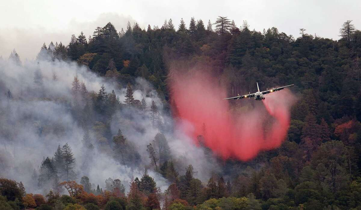 A firefighting plane drops a load of fire retardant over a smoldering hillside on Sept. 15, 2015 in Middletown, Calif.