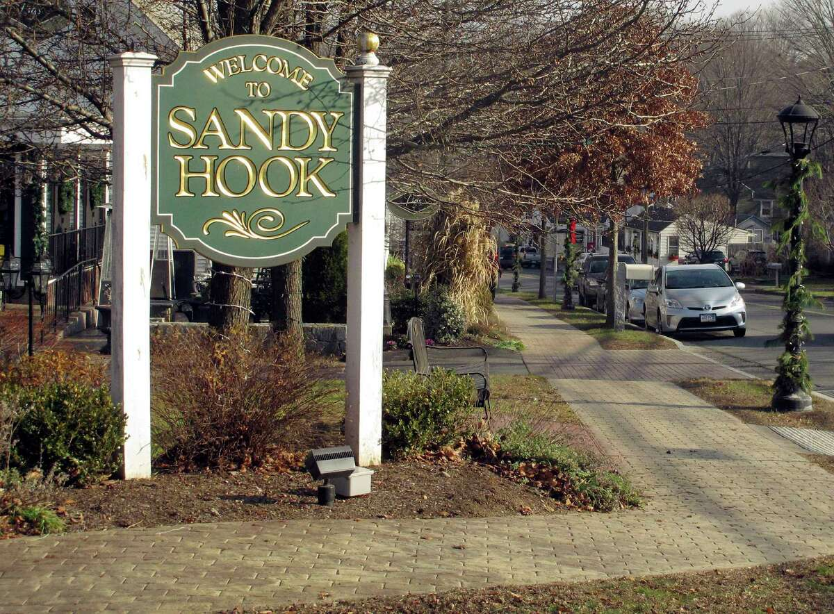 In this Dec. 11, 2015 photo, a sign welcomes people to the village of Sandy Hook in Newtown, Conn. An interfaith service is planned Monday evening, Dec. 14, on the third anniversary of the shooting at Sandy Hook Elementary School that killed 20 first-graders and six educators. Monday is also the first time the anniversary falls on a school day.