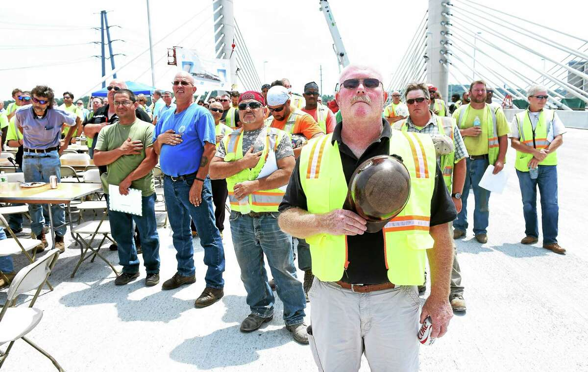 """Jim Doheny, center, business manager for Local 424 of the Iron Workers Union, and construction workers who worked on the Pearl Harbor Memorial Bridge stand at attention during the playing of """"The Star Spangled Banner"""" following a barbecue lunch on top of the bridge in New Haven Friday."""