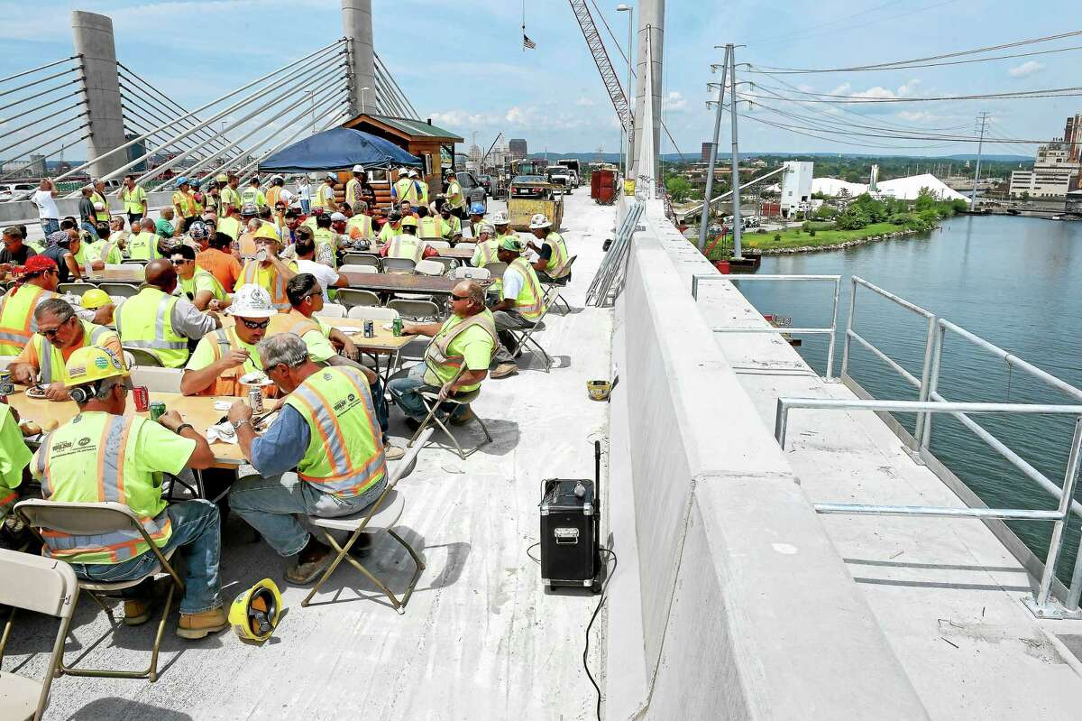 Construction workers celebrate the completion of southern half of the Pearl Harbor Memorial Bridge with a barbecue lunch on top of the bridge Friday in New Haven.