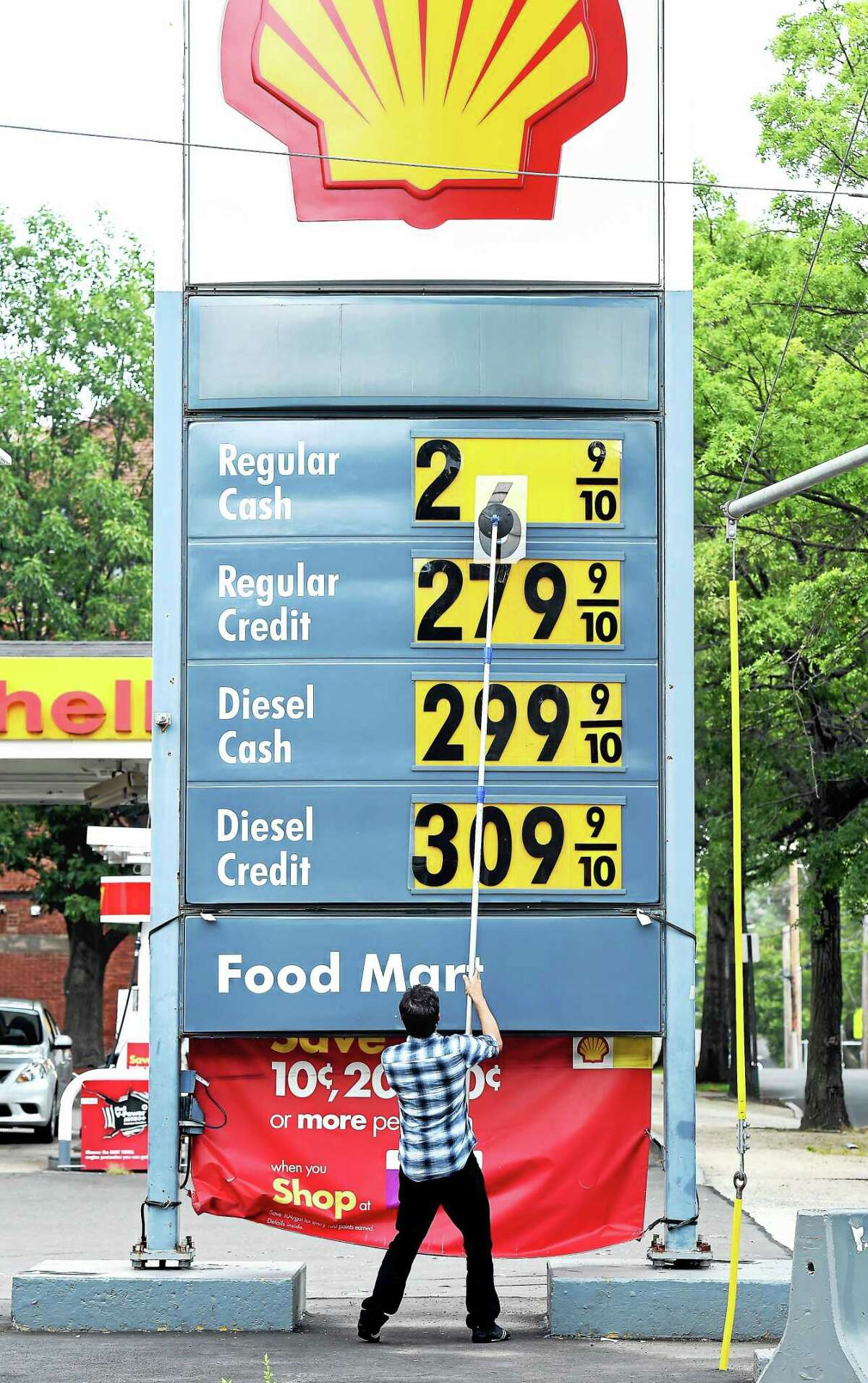 Manager Syed Naqshband lowers the price of a gallon of gasoline by 6 cents at Gerry's Shell Food Mart on Willow Street in New Haven Monday.