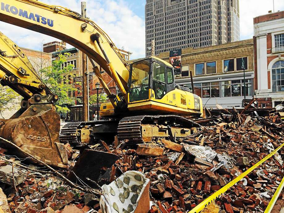 A large pile of debris remained at the corner of Chapel and Orange streets in New Haven where a building had to be torn down Sunday night after it became unstable. Photo: Wes Duplantier — New Haven Register