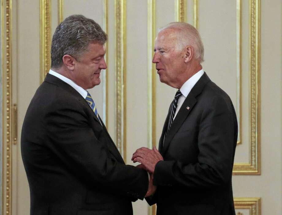 Ukrainian President Petro Poroshenko, left, and Vice President Joe Biden shake hands during their meeting in the presidential office in Kiev, Ukraine, last year. Photo: File   / AP