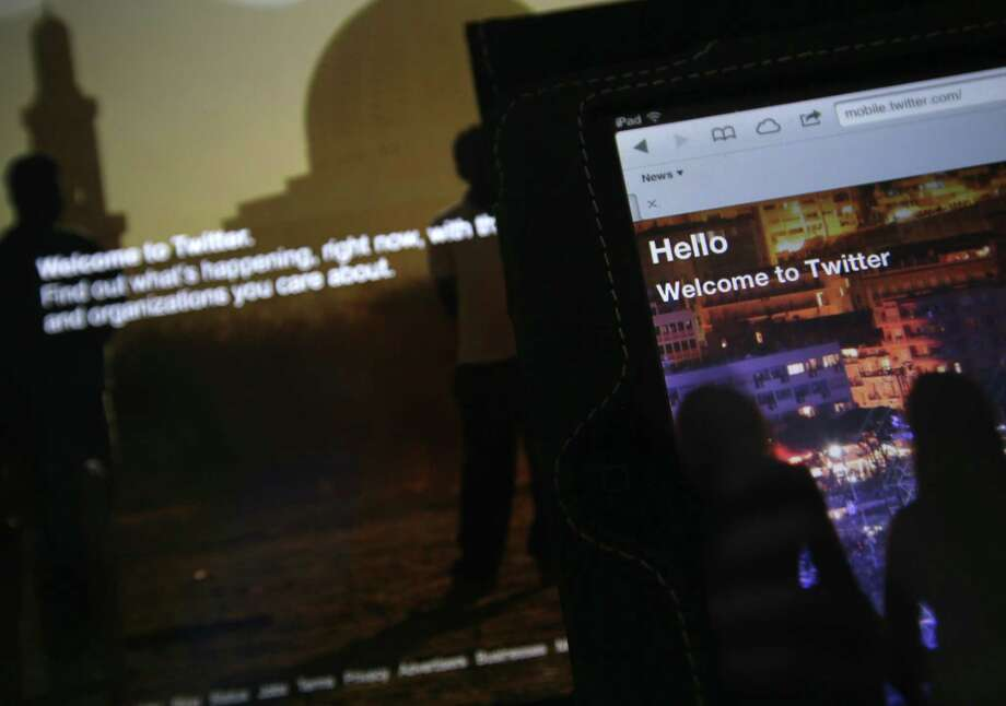 In this 2013 photo-illustration, the home page for Twitter is displayed on an iPad and a laptop computer. If Twitter is the chirping chatterbox of the Internet, trolls are its dark underground denizens. Photo: AP Photo   / AP