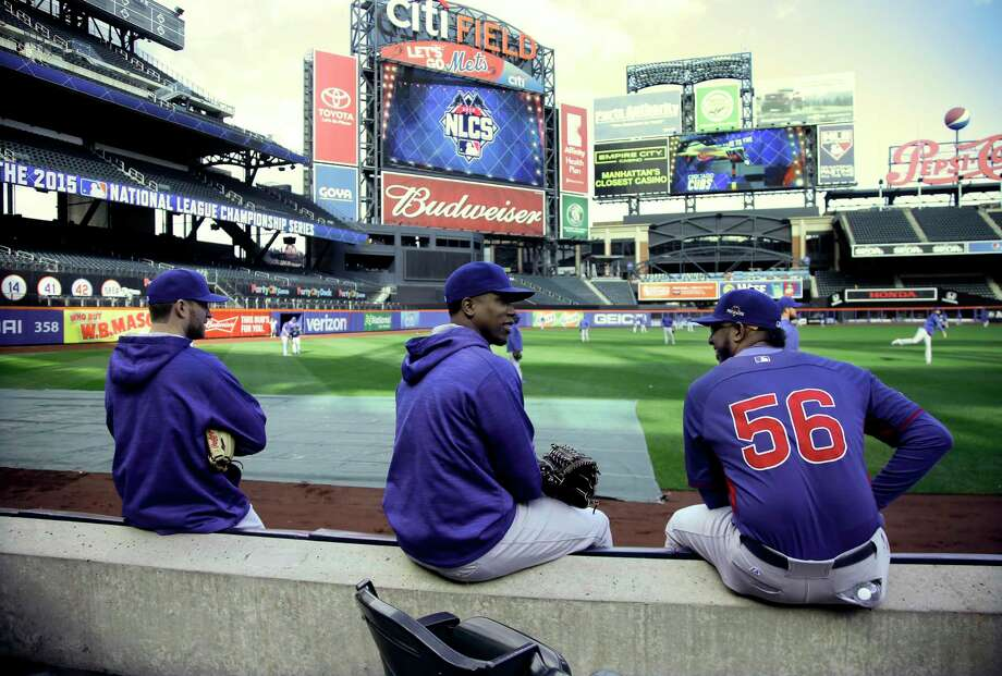 From left, Chicago Cubs pitcher Justin Grimm, catcher Miguel Montero and pitcher Hector Rondon take a break during batting practice Friday at Citi Field. The Cubs will face the New York Mets in Game 1 of the NLCS tonight. Photo: Julie Jacobson  — The Associated Press   / AP