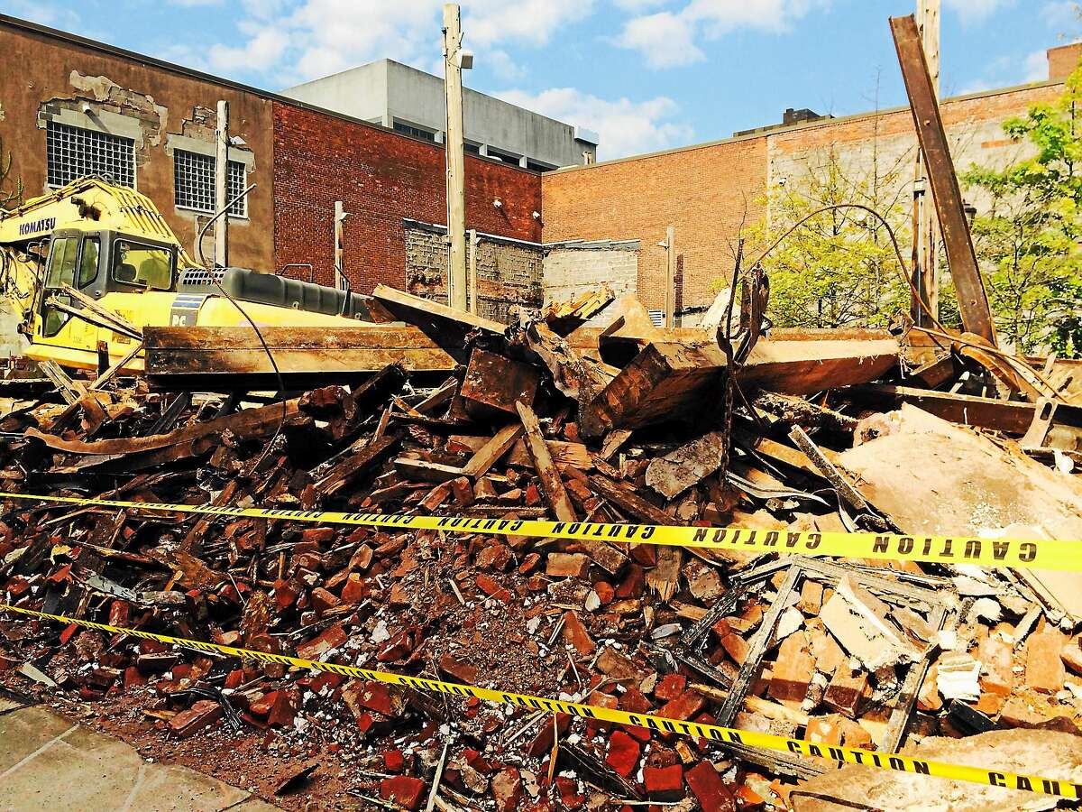 A large pile of debris remained at the corner of Chapel and Orange streets in New Haven Tuesday, after a building had to be torn down Sunday night after it became unstable.