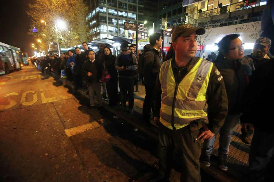 A police officer stands in the street to direct traffic as people stand in a line for public transportation after an earthquake in Santiago, Chile, Wednesday. Photo: Luis Hidalgo — The Associated Press   / AP