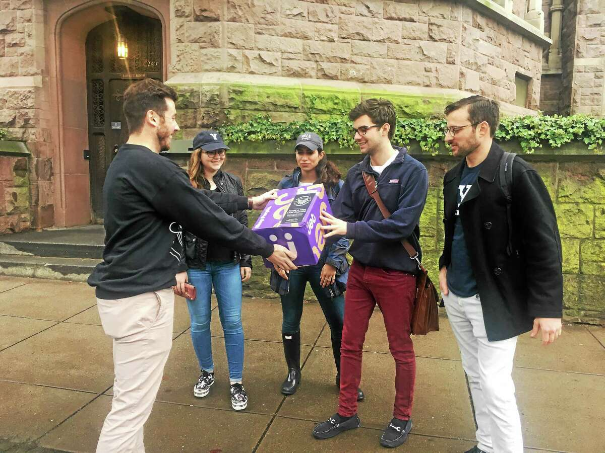 (Contributed photo) > Uber Connecticut General Manager Matthew Powers hands a care package to Yale Student Louis Pappas.