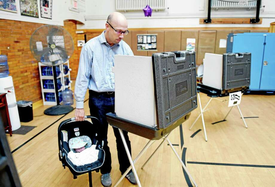 Sean Hundtofte carries his two-week-old daughter, Hazel, to vote with him at the Atwater Senior Center in New Haven Wednesday. Photo: Arnold Gold — New Haven Register
