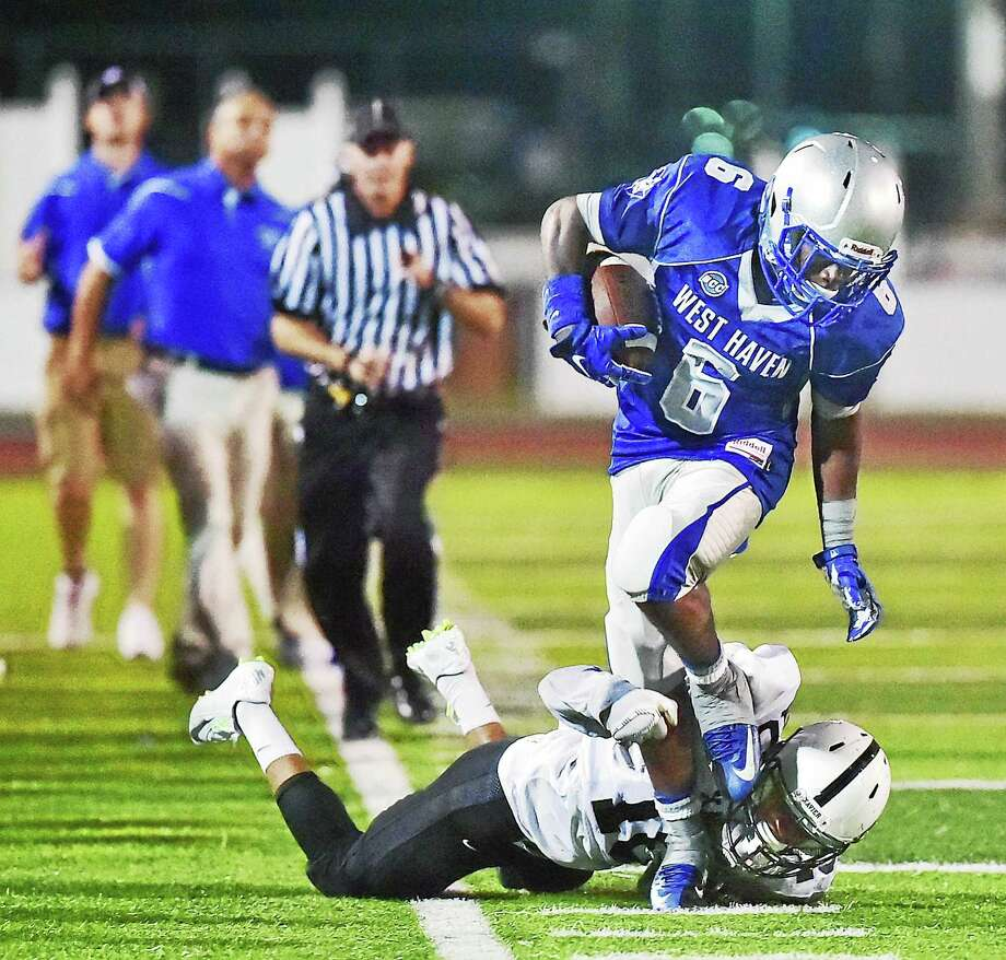 West Haven's Anthony Godfrey breaks loose from a Xavier defenseman in the season opener, Friday, September 11, 2015, at West Haven High School. The Westies defeated the Falcons, 35-27. (Catherine Avalone/New Haven Register) Photo: Journal Register Co. / New Haven RegisterThe Middletown Press