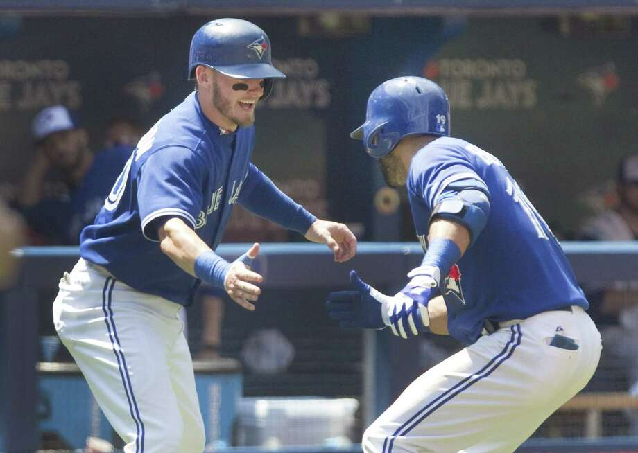 Jose Bautista, right, is met by teammate Josh Donaldson after hitting two-run home run in the third inning Sunday. Photo: Fred Thornhill — The Canadian Press Via AP   / The Canadian Press