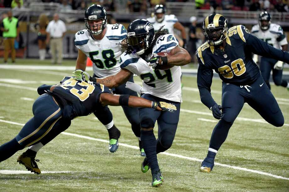 Seattle Seahawks running back Marshawn Lynch (24) runs with the ball as Rams free safety Rodney McLeod (23) and defensive tackle Michael Brockers (90) defend during Sunday's game in St. Louis. Photo: L.G. Patterson — The Associated Press   / FR23535 AP
