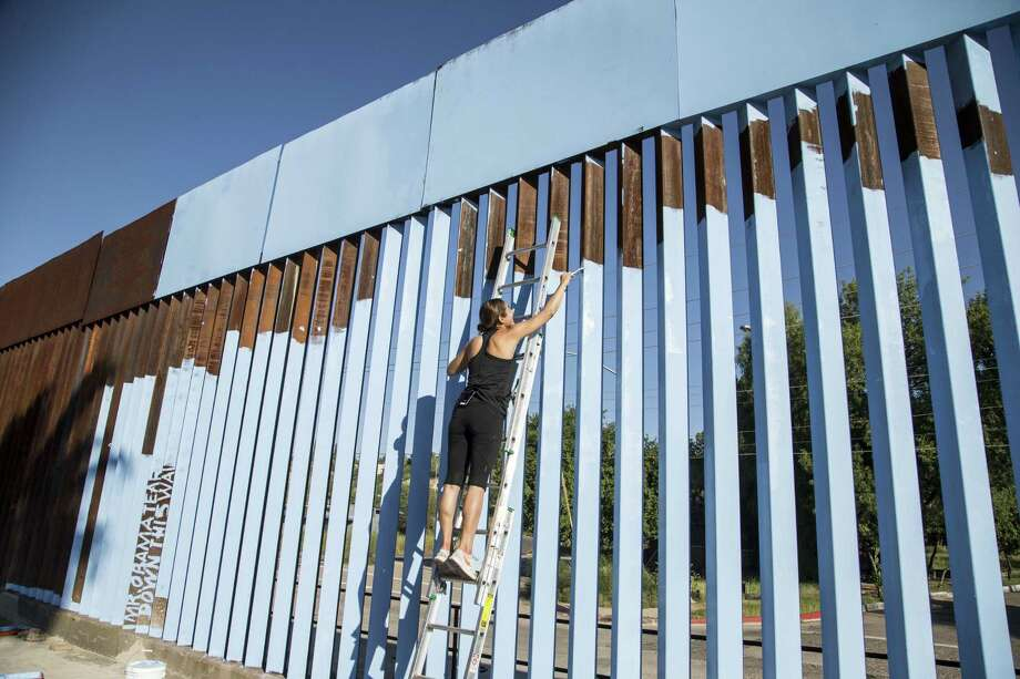 Artist Ana Teresa Fernández  paints the border fence that splits up Mexico and the U.S., in Nogales, Mexico. Fernández, who was born in Mexico but raised in San Diego, is leading an effort to paint the border fence in Nogales, Sonora, so blue that it blends with the sky, rendering it nearly invisible. Nogales sits on the border with Nogales, Arizona. Photo: Nick Oza — The Arizona Republic Via AP   / The Arizona Republic