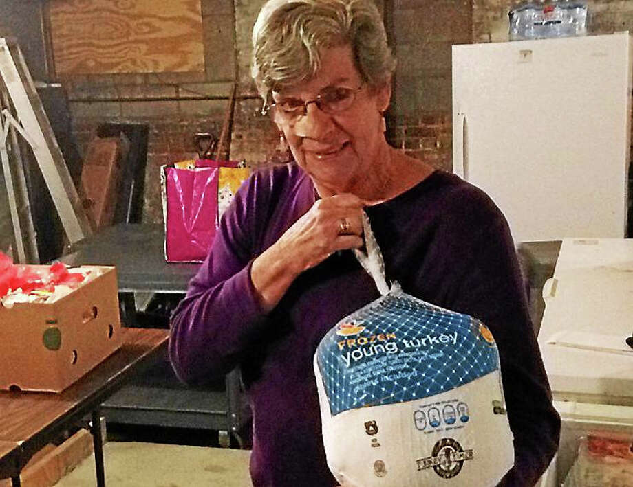 Wendy Cowles, president of the Branford Food Pantry, holds a frozen turkey taken from one of the pantry freezers. Photo: Juliemar Ortiz — New Haven Register