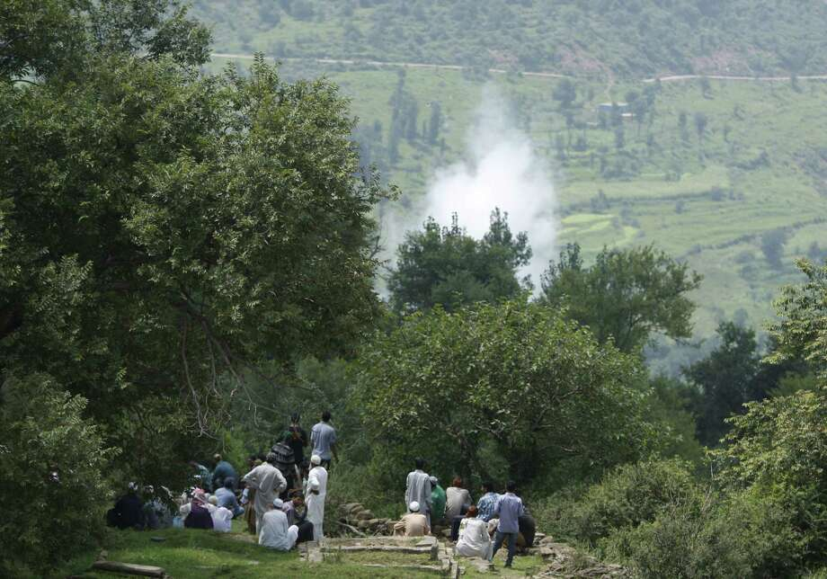 Smoke rises behind from a mortar shell fired by Pakistani troops as Indian villagers sit during the funeral of Indian civilian Sarpanch Karamat Hussain who was killed in Pakistani shelling at Balakot sector in Poonch, Jammu and Kashmir, India on Aug.16, 2015. Indian and Pakistani troops traded heavy gunfire and mortar rounds for a seventh day Sunday along the highly militarized line of control dividing the disputed Himalayan region of Kashmir between the two archrivals, officials said. Photo: AP Photo/Channi Anand   / AP
