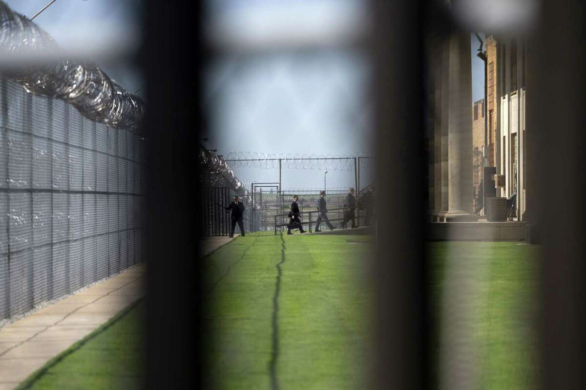White House staff walk into the El Reno Federal Correctional Institution in El Reno, Okla., Thursday, July 16, 2015. As part of a weeklong focus on inequities in the criminal justice system, the president will meet separately Thursday with law enforcement officials and nonviolent drug offenders who are paying their debt to society at the El Reno Federal Correctional Institution, a medium-security prison for male offenders near Oklahoma City. (AP Photo/Evan Vucci)