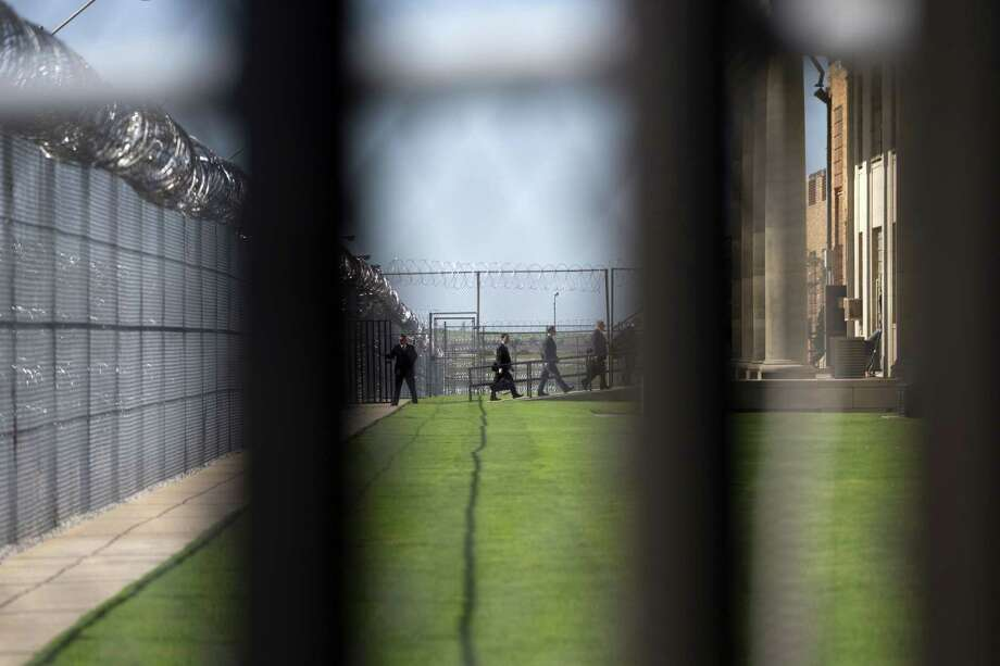 White House staff walk into the El Reno Federal Correctional Institution in El Reno, Okla., Thursday, July 16, 2015. As part of a weeklong focus on inequities in the criminal justice system, the president will meet separately Thursday with law enforcement officials and nonviolent drug offenders who are paying their debt to society at the El Reno Federal Correctional Institution, a medium-security prison for male offenders near Oklahoma City.  (AP Photo/Evan Vucci) Photo: AP / AP