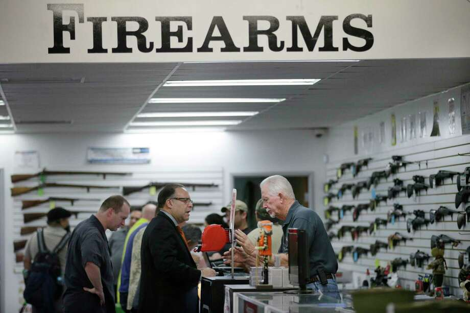 In this Dec. 9, 2015 photo, sales associate Mike Conway, right, shows Paul Angulo a pistol at Bullseye Sport gun shop in Riverside, Calif. Photo: AP Photo/Jae C. Hong   / AP