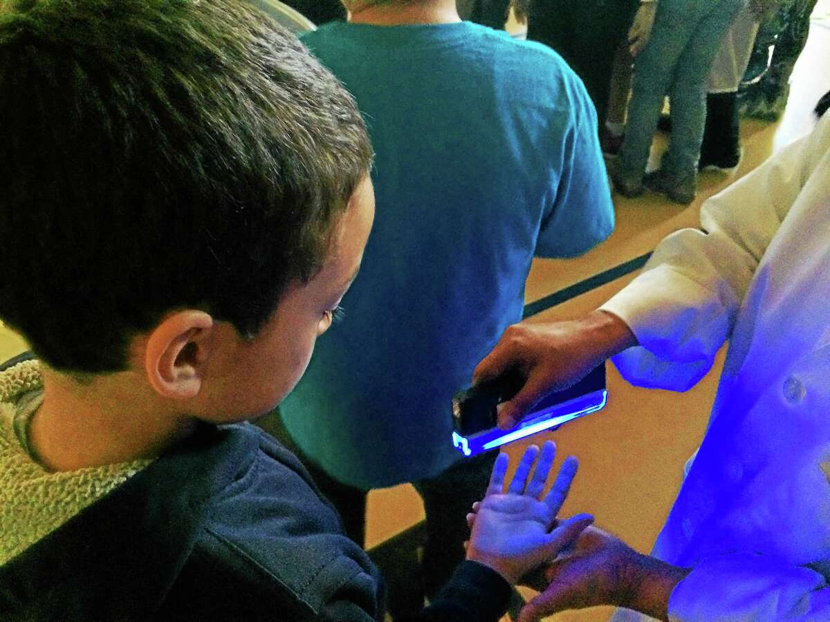 Fourth-grader Fernando Ovalle checks out before-and-after effects of hand washing on skin bacteria under UV light