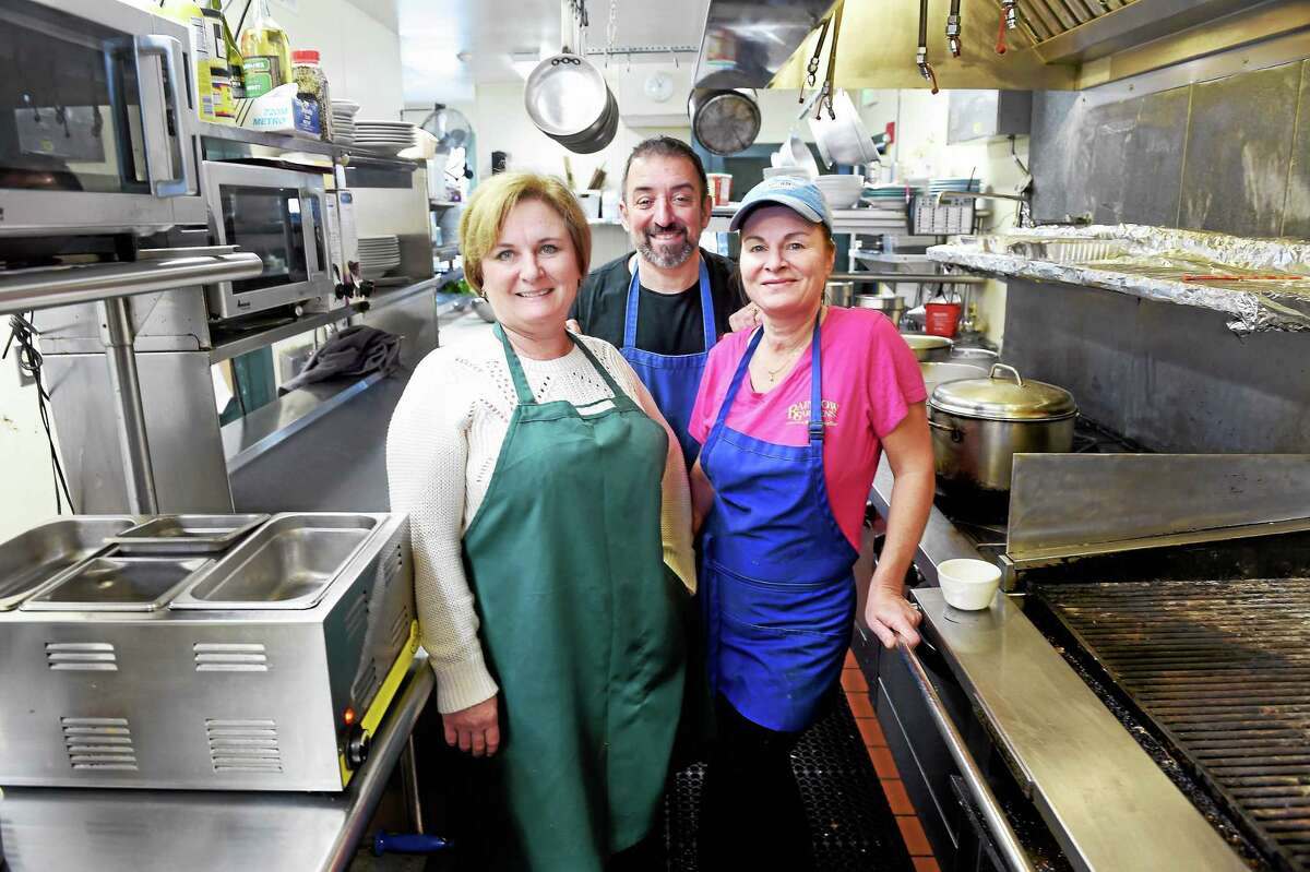 (Arnold Gold-New Haven Register) From left, Rainbow Gardens Restaurant & Bar owners Heather Profetto, her husband, John, and head chef Kate Campbell pause in the restaurant's kitchen in Milford.