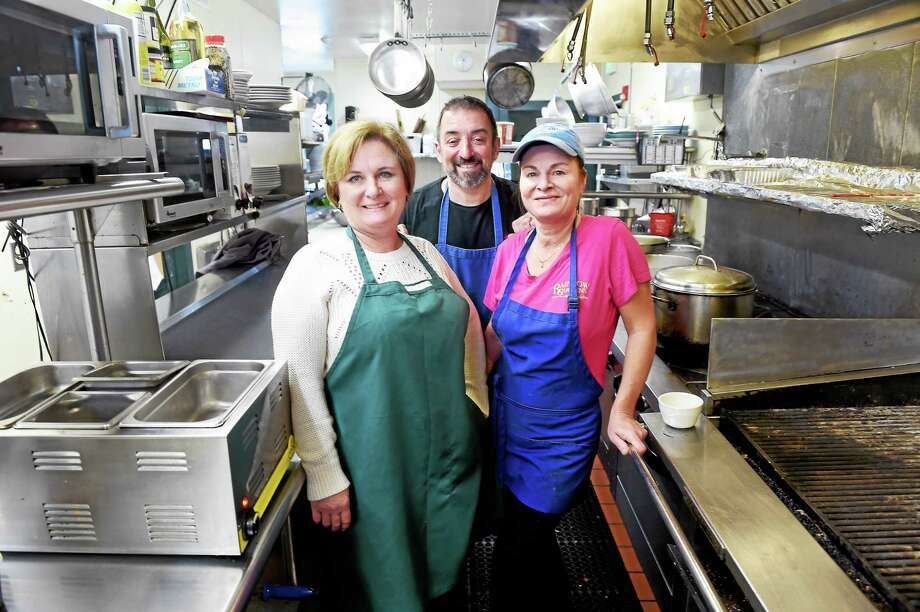 (Arnold Gold-New Haven Register)  From left, Rainbow Gardens Restaurant & Bar owners Heather Profetto, her husband, John, and head chef Kate Campbell pause in the restaurant's kitchen in Milford. Photo: Journal Register Co.