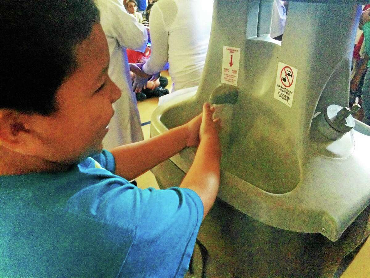 First-grader Yuxiu Chen washes his hands.