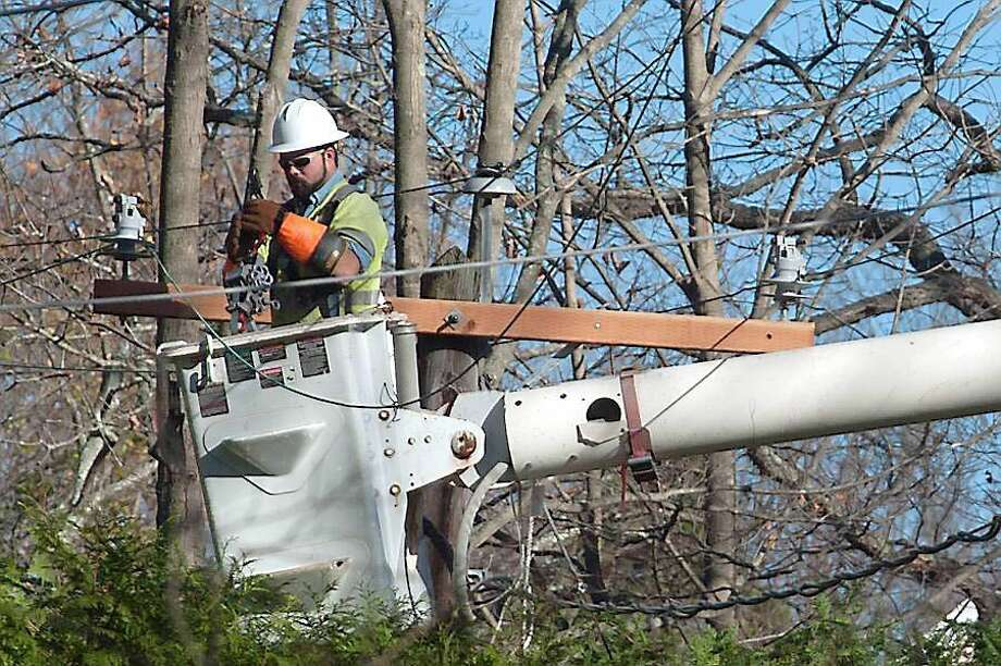 A lineman re-rigs electrical lines. Haddam and Old Saybrook were hit by power outages Tuesday. Photo: File