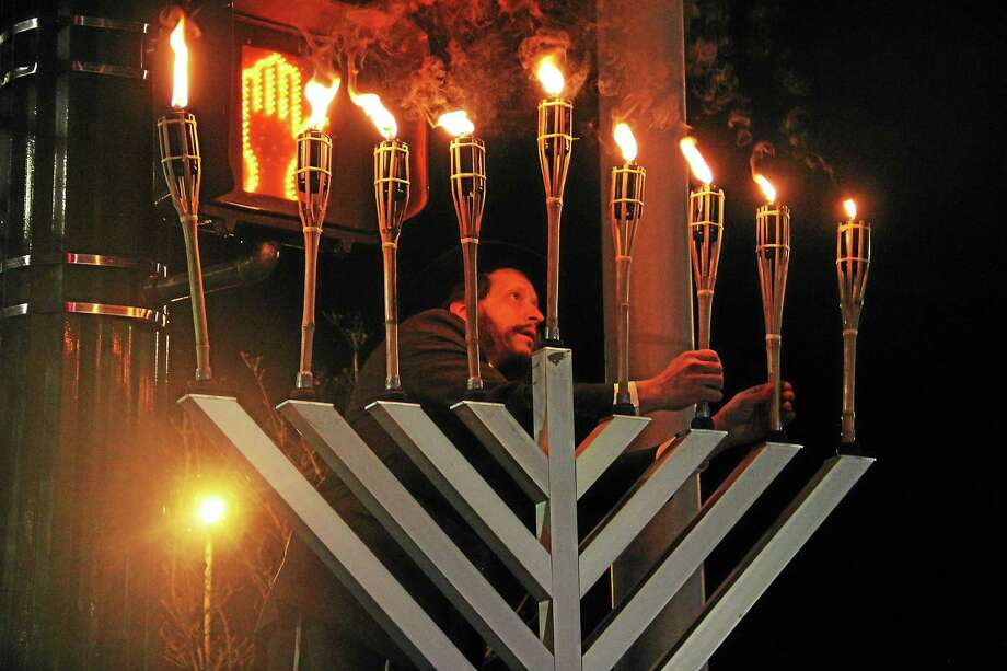 Esteban Hernandez --- New Haven Register  Rabbi Yossi Hodakov of Chabad of Westville examines a menorah during the final night of Hanukkah event at the Whalley-Blake lot on Sunday. Photo: Journal Register Co.